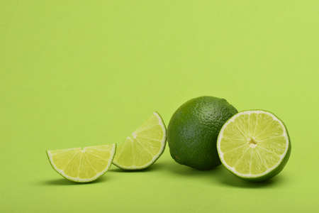 Lime with slices on green background