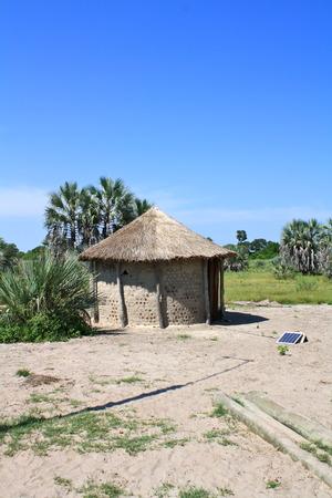 Barro con tejado de paja Rondavel con panel solar Foto de archivo - 33968523