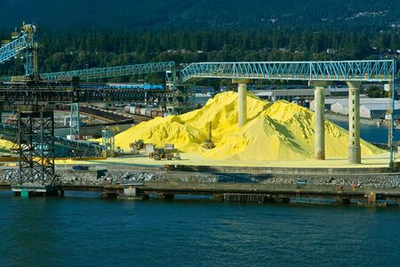 Bright yellow sulfur piles in at the water in Vancouver harbor, Canada.