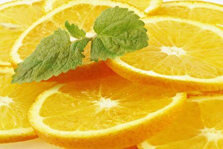 The leaves of mint lying on orange segments. Fruit background. photo