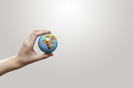 holding a earth ball in hands on gray background photo