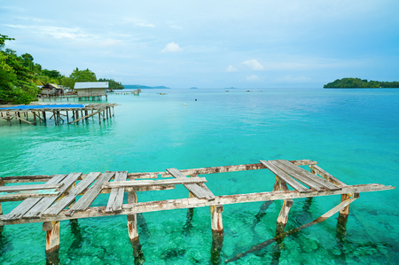 Old wooden piers on the background of clear turquoise ocean water
