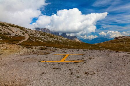The site with a yellow sign on a background of mountain peaks and blue cloudy sky