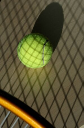 strains: Tennis ball with shadow of a tennis racket Stock Photo