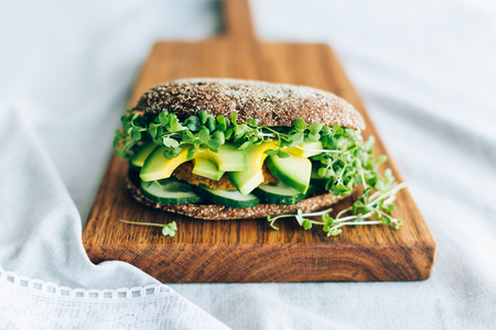 Vegetarian burger with cucumber, avocado, microgreen mustard on a wooden board