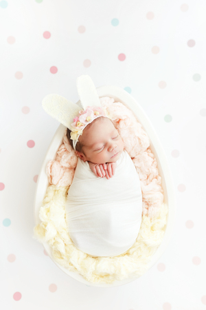 Easter bunny newborn baby girl in a wooden egg on a white background in peas