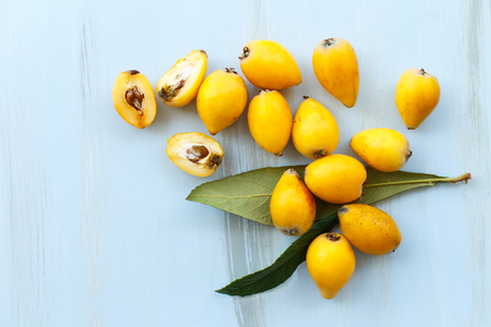 Loquat orange fruits on branch with leaves on a blue wooden background