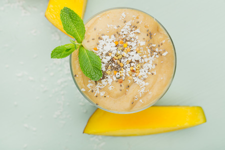 A glass of fruit smoothie on a blue wooden table with pieces of mango, with coconut shavings and a sprig of mint. Concept of healthy eating, top view, close-up. 写真素材