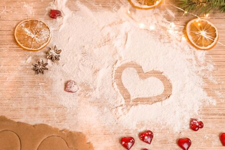 The concept of baking for Valentine's Day with torches in the shape of a heart . the heart is drawn on the flour in the process of making cookies.