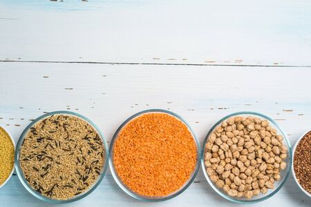 Varieties of natural organic seed in round plates of lentils, chickpeas and brown long rice . the view from the top. space for text. healthy veggie food . diet.