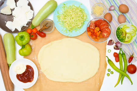step by step recipe for cooking homemade vegan pizza with zucchini, tomatoes, peppers, mozzarella. hands of a woman preparing a pizza from the top view. light background.