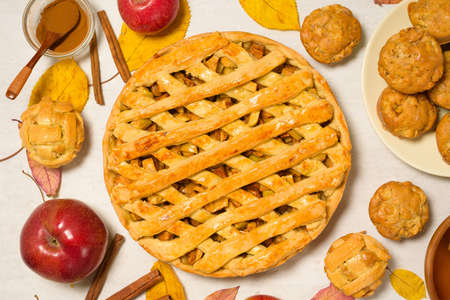 autumn baking concept with seasonal apples and cinnamon honey. Apple pie, muffins, cupcakes. top view on a light background with autumn yellow leaves