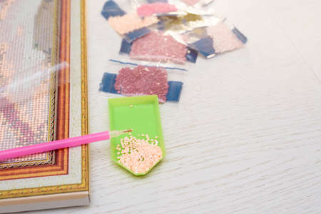 home hobby to draw a picture of rhinestones, multicolored diamond mosaic. the process of gluing a pencil of rhinestones on the canvas of the picture.