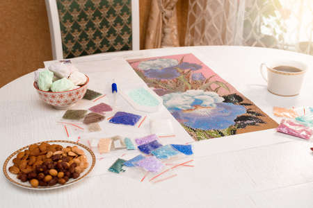 home hobby-to draw pictures of rhinestones, multi-colored diamond mosaic. the process of gluing pencil rhinestones on canvas pictures of the house on the table with tea and nuts. Foto de archivo