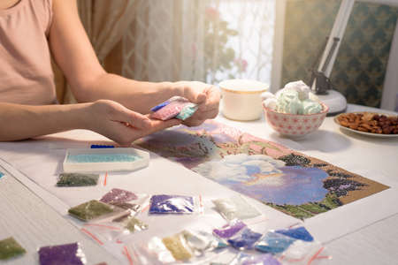 home hobby-to draw pictures of rhinestones, multi-colored diamond mosaic. the process of gluing pencil rhinestones on canvas pictures of the house on the table with tea and nuts.