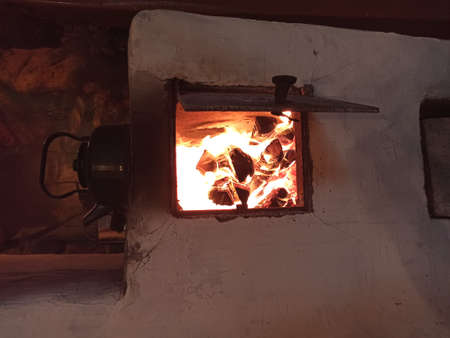 Old traditional russian stone stove with kettle and firewood. Peasants life village. Wood heating of izba, hut. Baking oven. Oven for cooking.