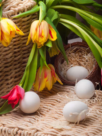 delightfully: white eggs and spring tulips basket on straw tray