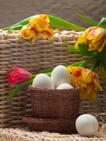 delightfully: white eggs in small brown and spring tulips basket on straw tray