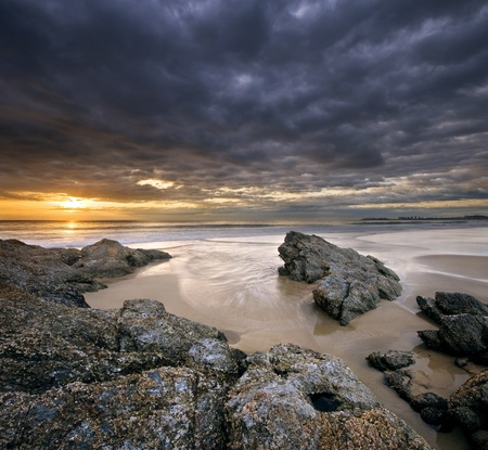 rocks on beach at sunrise with dramatic sky on square format