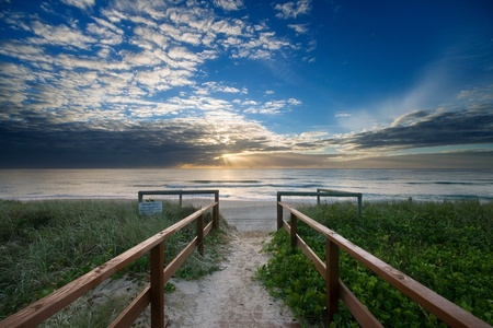 entry to beach with leading handrails towards sunrise  photo