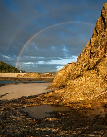 cliff face: cliff face with rainbow in background Stock Photo