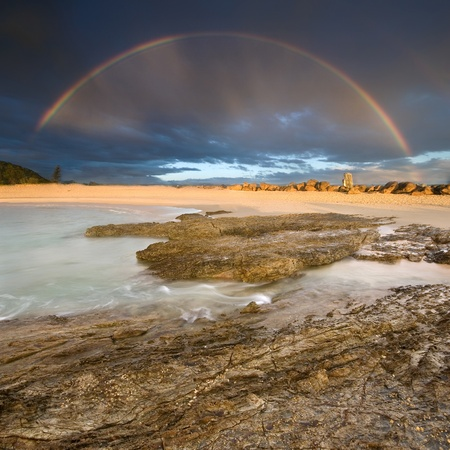 Rainbow with rock in foreground at cloudy morning Stock Photo