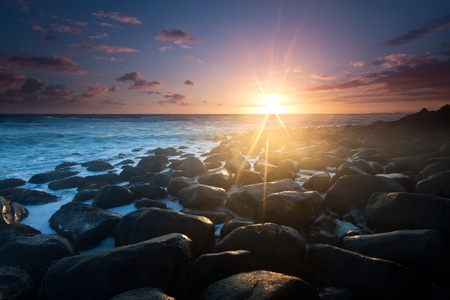 sunrise with interesting full of rocks foreground and nice clouds color in background