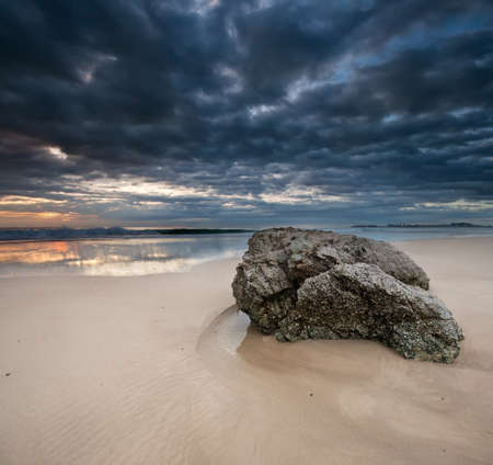 Rock on the beach with dramatic sky on square format photo