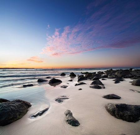 interesting beach at twilight with rocks in foreground photo