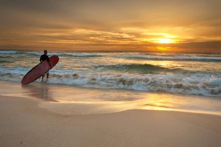 Surfer entrando el océano al amanecer para have some fun