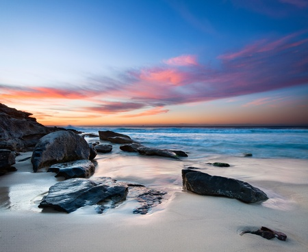 interesting beach with rocks in foreground and red clouds on sky photo