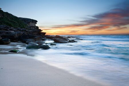 cliff face: australian beach at dawn with cliff face in background