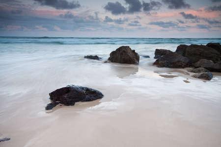 rocks on the beach at twilight photo