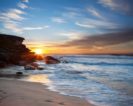 australian beach at sunrise with rushing wave in foreground