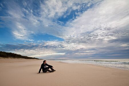 a boy on the isolated australian beach with big clouds in background