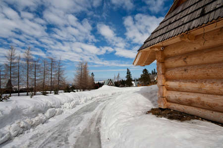 traditional polish hut in zakopane during winter season with unsealed road in foreground Stock Photo - 8603619