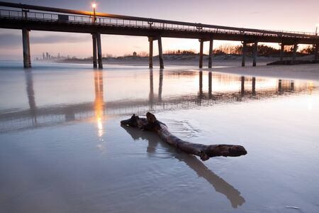 log on beach at twilight with pier and the city in background photo