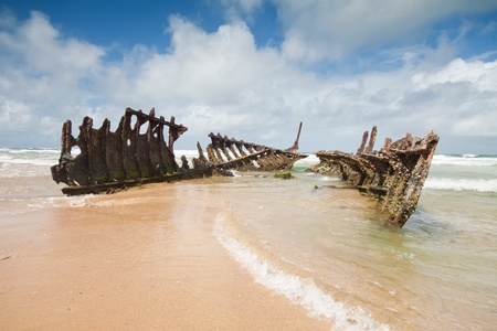 wreck on australian beach during the day (dicky beach, queensland) with interesting cloud formation in background