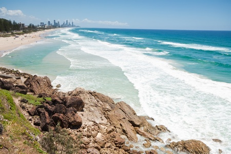 australian beach during the day with rock cliff in foreground (miami beach,qld)