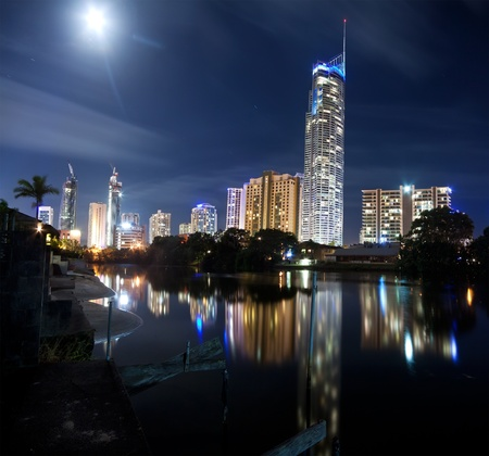 modern city at night with building in foreground on square format (gold coast, australia) photo