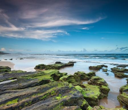 headland: australian beach at twilight with interesting rocks in foreground (alexandra headland,qld,australia)