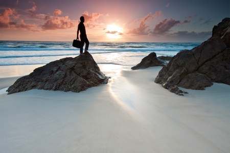 man is holding his laptops bag when standing on top of the rock at sunrise (miami beach,queensland,australia)