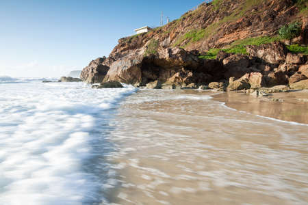 australian seascape with rushing wave in foreground and cliff face beside (miami beach,qld,australia) Stock Photo - 9056634