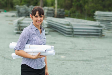 earing: young engineer woman supervising yard with rolled drawings in her hand Stock Photo
