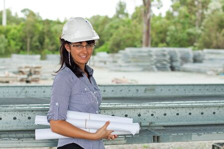 smiling young engineer woman with rolled drawings in her hands who wears glasses and helmet in the warehouse photo