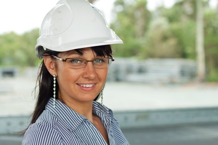 smiling young engineer woman wears glasses and helmet in the warehouse photo