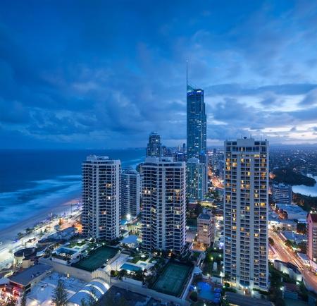 strand australie: uitzicht over de moderne stad in de schemering met Oceaan naast op vierkant formaat (gold coast, queensland, Australië)