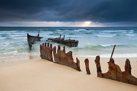 wreck on australian beach at sunrise (ss dicky wreck,dicky beach, queensland)