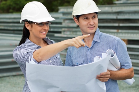 young engineer woman shows her co-worker around the on site standing with drawings