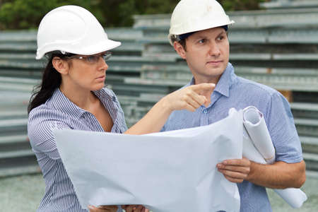 young engineer woman shows her co-worker around the site holding drawings